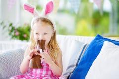 Oavbrutet tjata bärande kaninöron för den gulliga lilla flickan som äter chokladpåsk Unge som spelar äggjakt på påsk Arkivfoto