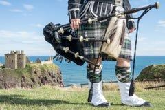 Oavkortad klänningkod för traditionell skotsk säckpipeblåsare på den Dunnottar slotten Arkivbilder