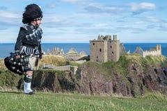 Oavkortad klänningkod för traditionell skotsk säckpipeblåsare på den Dunnottar slotten Arkivfoto