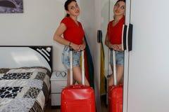Oavkortad längd för ung tillfällig flicka med resväskan i hotell Arkivbilder