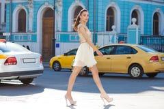 Oavkortad tillv?xt f?r st?ende, ung h?rlig brunettkvinna i rosa kl?nning royaltyfria bilder