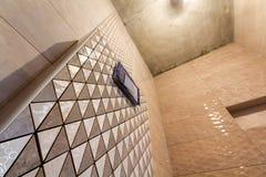 Oavslutad rekonstruktion av badrummet eller toaletten med keramiska tegelplattor f?r ljus beige geometrisk mosaik som installeras royaltyfri fotografi