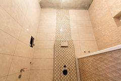 Oavslutad rekonstruktion av badrummet eller toaletten med ljusa beigea geometriska keramiska tegelplattor som installeras p? v?gg royaltyfri fotografi