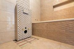 Oavslutad rekonstruktion av badrummet eller toaletten med ljusa beigea geometriska keramiska tegelplattor som installeras p? v?gg royaltyfria bilder