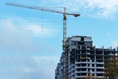 Oavslutade byggnadskonstruktion och byggnadskranar mot klar bakgrund för blå himmel Arkivfoto