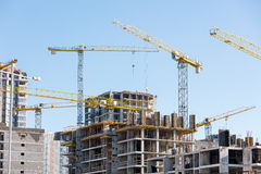 Oavslutade byggnadskonstruktion och kranar mot klara blått s Arkivfoto