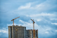 Oavslutade höghus och kranar mot himlen Fotografering för Bildbyråer
