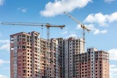 Oavslutade höghus och tornkranar på backg för blå himmel Arkivbild