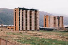 Oavslutade mång--berättelse hus på bergbakgrund arkivbild