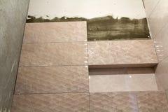 Oavslutat arbete, ljusa beigea keramiska tegelplattor som installeras p? v?ggar av badrummet, eller toalett Bel?gger med tegel in royaltyfria bilder