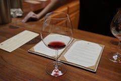 Oavslutat exponeringsglas av ett rött vin i en restaurang arkivfoto