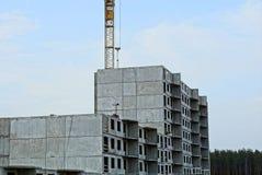 Oavslutat högväxt hus med en tornkran mot himlen arkivbilder