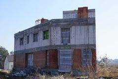 Oavslutat hus av vit och brun tegelsten med tomma fönster på byggandeplatsen arkivbild