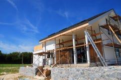 oavslutat hus Hem- omdana och renovering Måla husväggen med stuckaturen och rappa Isoleringshusvägg arkivfoto