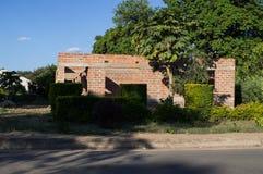Oavslutat hus i en bostads- gata, Livingstone, Zambia arkivfoto