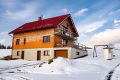 Oavslutat hus under konstruktion under vinter med snö omkring arkivfoto