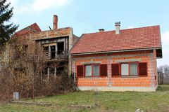 Oavslutat nytt förorts- hus bredvid gammalt förstört hus royaltyfria bilder
