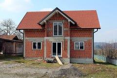 Oavslutat tegelstenhus med röda taktegelplattor arkivfoton