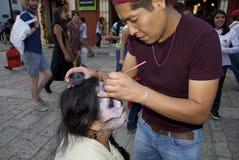 Oaxaca, 1 Mexico-November, 2016: Een vrouw krijgt haar die make-up voor dag van de doden wordt gedaan Royalty-vrije Stock Afbeeldingen