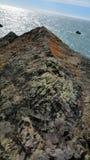 Oböjlig klippkant som sticker ut ut över havet Royaltyfri Foto