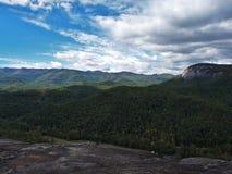 Obłoczne formacje nad pasmem górskim z rockową twarzą i drzewami Zdjęcie Royalty Free