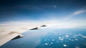 Obłoczny niebieskiego nieba i samolotu skrzydłowy widok Zdjęcie Stock
