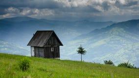 Obłoczny ruch nad starym drewnianym małym domem przeciw góry tłu zbiory wideo