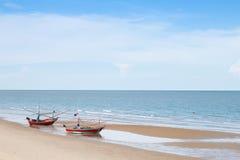 Oba drewniana łódź rybacka na plaży z niebieskim niebem Obrazy Stock