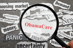 Obama Care headline. Magnifying glass looking at newspaper headlines, with ObamaCare in red Royalty Free Stock Images