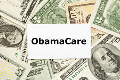 ObamaCare Concept. ObamaCare printed on white card with US bills as a background Stock Images