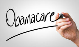 Obamacare hand writing with a black mark on a transparent board Royalty Free Stock Photography