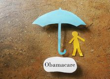Obamacare health insurance. Paper person under an Obamacare umbrella - Affordable Care Act concept Royalty Free Stock Photos