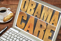 Obamacare letterpress typography on laptop screen. Obamacare typography - word abstract in letterpress wood type on a laptop screen with a cup of coffee Royalty Free Stock Photo