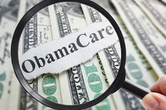 Obamacare and magnifying glass. Obamacare newspaper headline on cash with magnifying glass Royalty Free Stock Photo
