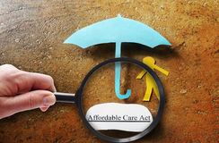 Obamacare research. Paper person and Affordable Care Act umbrella under magnifying glass Stock Image