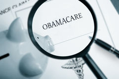 Obamacare search. Magnifying glass over Obamacare policy and piggy bank Royalty Free Stock Photo
