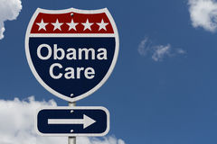 ObamaCare Sign. A red, white and blue highway sign with words ObamaCare and an arrow sign with sky background Royalty Free Stock Photo