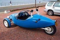 Oban,英国- 2010年2月20日:在停车处的蓝色汽车在海码头 大酒杯有三个轮子的avion汽车 免版税库存图片