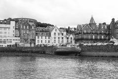 Oban Förenade kungariket - Februari 20, 2010: fjärd med hus på grå himmel Stadsarkitektur längs havskajen tillgripa townen royaltyfria bilder