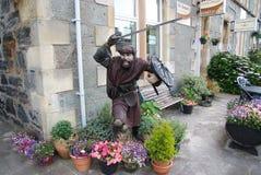 Oban Förenade kungariket - Februari 20, 2010: krigarestaty på byggnadshörn med krukväxter Radhus med bänken och Royaltyfria Bilder