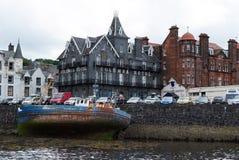Oban Förenade kungariket - Februari 20, 2010: skeppsbrott- och stadsarkitektur längs havskajen Fjärd med hus på grå himmel Royaltyfri Bild