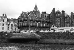 Oban, het Verenigd Koninkrijk - Februari 20, 2010: schipbreuk en stadsarchitectuur langs overzeese kade Baai met huizen op grijze royalty-vrije stock afbeeldingen