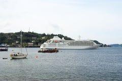 Oban, Regno Unito - 20 febbraio 2010: le imbarcazioni in mare lungo la montagna costeggiano la nave da crociera e le barche a vel Immagini Stock Libere da Diritti