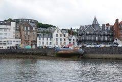 Oban, Reino Unido - 20 de fevereiro de 2010: baía com as casas no céu cinzento Arquitetura da cidade ao longo do cais do mar Estâ Fotografia de Stock Royalty Free