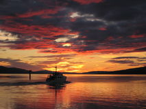 Oban Sunset. This is Oban harbour (North of Scotland) at sunset with the Poplar voyager sailing past Stock Image
