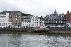 Oban, United Kingdom - February 20, 2010: bay with houses on grey sky. City architecture along sea quay. Resort town. With hotels. Summer vacation on island Royalty Free Stock Photography