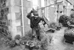 Oban, United Kingdom - February 20, 2010: warrior statue on building corner with pot plants. Town house with bench and. Flowers in yard. Victorian style royalty free stock photo