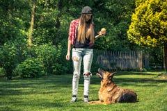 Obbedienza d'istruzione del cane della donna casuale autentica immagini stock