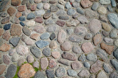 Сobblestones of the ancient city. Ancient paving stones. The cobblestones of the ancient city. Natural surface roads. Background and texture of the stones Royalty Free Stock Photography