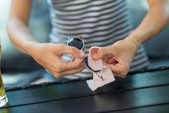 Obcieranie okulary przeciwsłoneczni - kobiety czyści słońc szkła z mikro włókna wytarciem zdjęcie royalty free